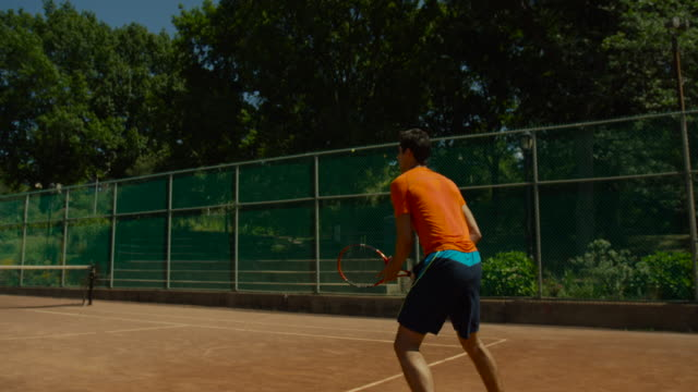 slow motion shot of man making low backhand return on clay tennis court - backhand bildbanksvideor och videomaterial från bakom kulisserna