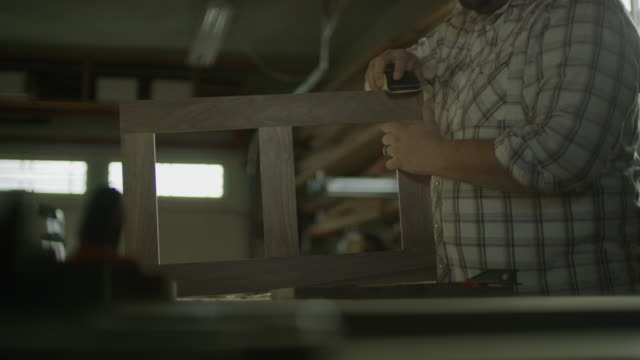 slow motion shot of man sanding wood frame in workshop / provo, utah, united states - provo stock videos & royalty-free footage