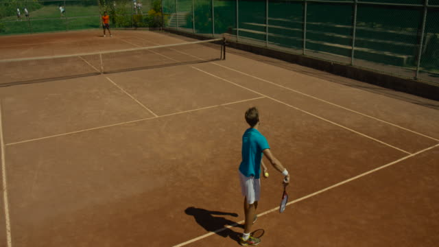 slow motion shot of man serving tennis ball to opponent on clay court - スポーツ競技点の映像素材/bロール