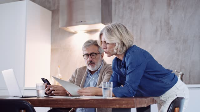 stockvideo's en b-roll-footage met slow motion shot of mature couple using laptop and checking documents - leesbril