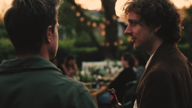 Slow motion shot of men with beer bottle talking in backyard during social gathering