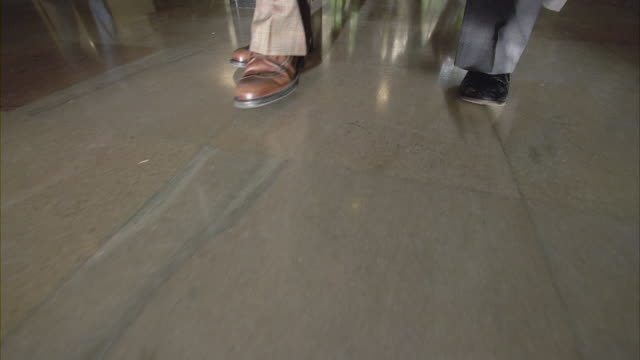 a slow motion shot of mens feet walking in the lobby of the cia headquarters. - seal stamp stock videos and b-roll footage