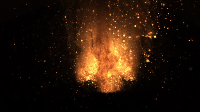 Slow motion shot of molten iron exploding in a small bowl.
