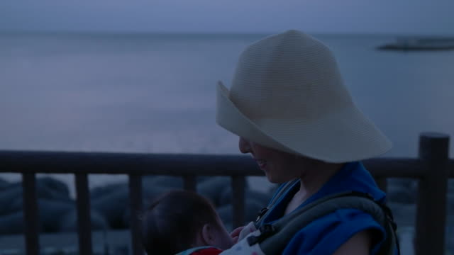 slow motion shot of mother and baby walking by beach side during sunset. - only japanese stock videos & royalty-free footage
