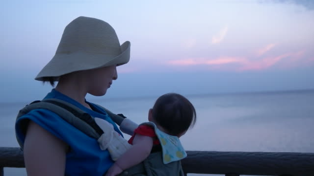 Slow motion shot of mother and baby walking by beach side during sunset.