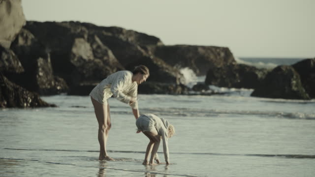 slow motion shot of mother and daughter holding hands and running on ocean beach / big sur, california, united states - camminare nell'acqua video stock e b–roll