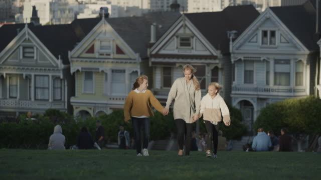slow motion shot of mother and daughters walking then running in park / san francisco, california, united states - tre fjärdedels längd bildbanksvideor och videomaterial från bakom kulisserna