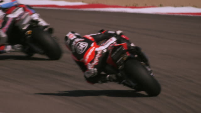 slow motion shot of motorcycle racers on the race track - competizione video stock e b–roll