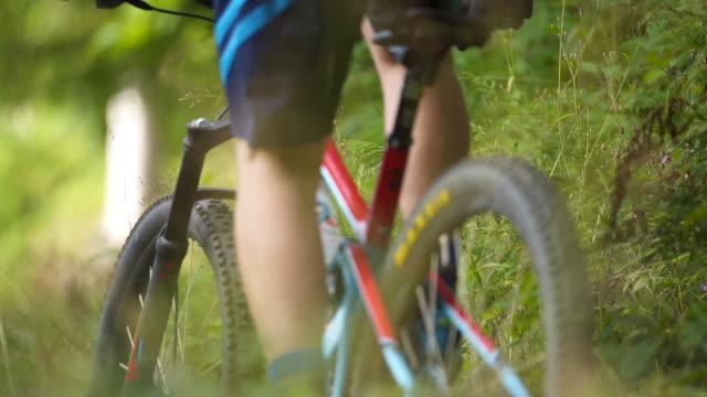 森の中を登山道を下るマウンテンバイクのスローモーションショット - サイクリングロード点の映像素材/bロール