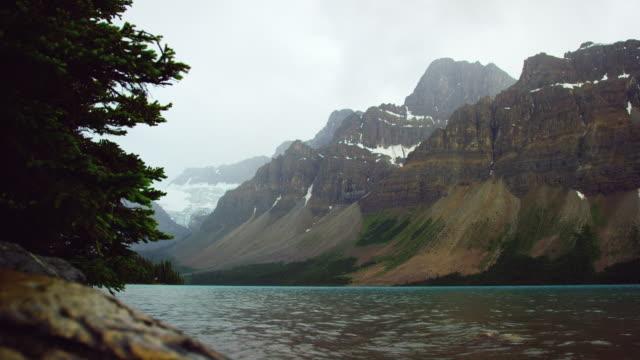 scatto al rallentatore del lago di montagna che si increspa dolcemente e spruzza con le montagne rocciose canadesi sullo sfondo nel jasper national park sotto un cielo nuvoloso in alberta, canada - riva dell'acqua video stock e b–roll