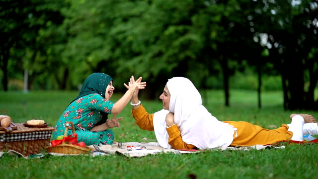 slow motion shot of muslim mother and daughter giving high five together at beautiful park - middle eastern culture stock videos & royalty-free footage