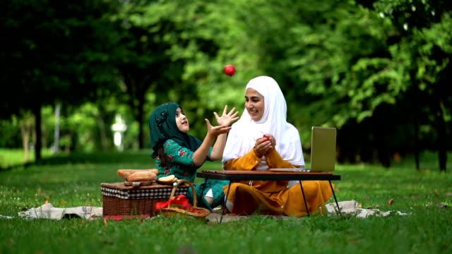vidéos et rushes de tir lent de mouvement de la mère et de la fille musulmanes jetant la pomme rouge dans l'air au beau parc - mode de vie actif