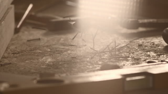 Slow motion shot of nails falling on a table in workshop