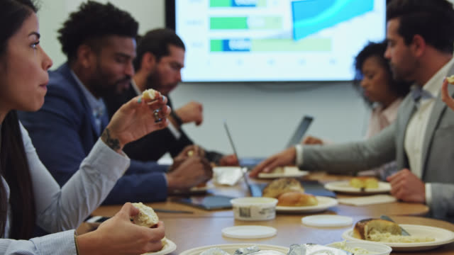 slow motion shot of office workers eating lunch at conference table - event stock videos & royalty-free footage