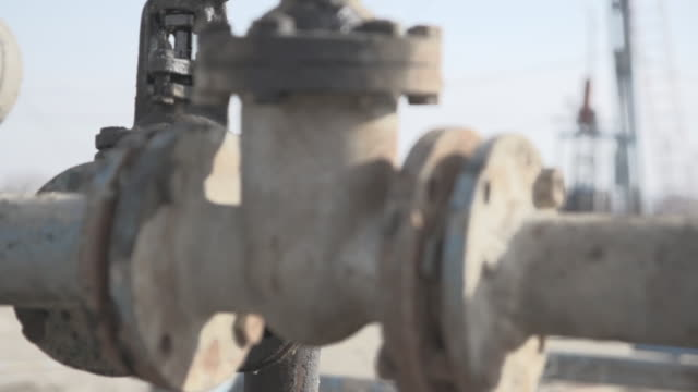 slow motion shot of oil pouring out of a pipe at an oil field near baku. - industria petrolifera video stock e b–roll