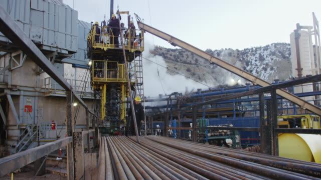 vídeos de stock, filmes e b-roll de tiro em câmera lenta de trabalhadores do campo de petróleo manipulando o tubo de perfuração um local de perfuração de óleo e gás em uma manhã fria e de inverno - boca de poço