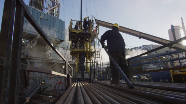 slow motion shot of oilfield workers rigging up drilling pipe on a tall, metal platform at an oil and gas drilling pad site on a cold, sunny, winter morning - safety stock videos & royalty-free footage