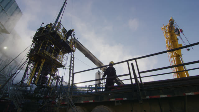 slow motion shot of oilfield workers rigging up drilling pipe on a tall, metal platform at an oil and gas drilling pad site on a cold, winter morning - mining stock videos & royalty-free footage