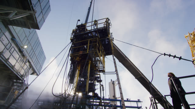 slow motion shot of oilfield workers rigging up drilling pipe on a tall, metal platform at an oil and gas drilling pad site on a cold, sunny, winter morning - arbeiter stock-videos und b-roll-filmmaterial