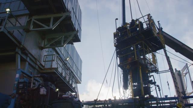 vídeos de stock, filmes e b-roll de tiro em câmera lenta de trabalhadores do campo de petróleo servindo um poço em uma plataforma alta e metálica em um local de perfuração de óleo e gás em uma manhã fria, ensolarada e de inverno - boca de poço
