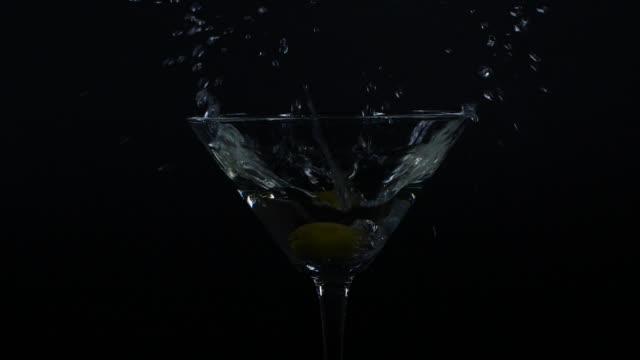 stockvideo's en b-roll-footage met langzame motiedie van olijf die neer in een glas martini valt - hd format