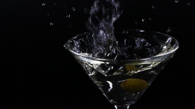 stockvideo's en b-roll-footage met slow motion schot van olijf die neer in een glas martini valt - hd format