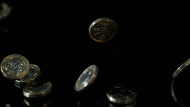 slow motion shot of one pound coins falling onto a reflective surface - super slow motion stock videos & royalty-free footage