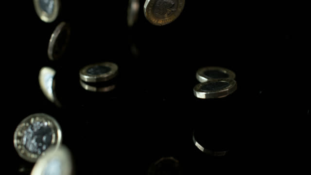 slow motion shot of one pound coins falling onto a reflective surface. - currency stock videos & royalty-free footage
