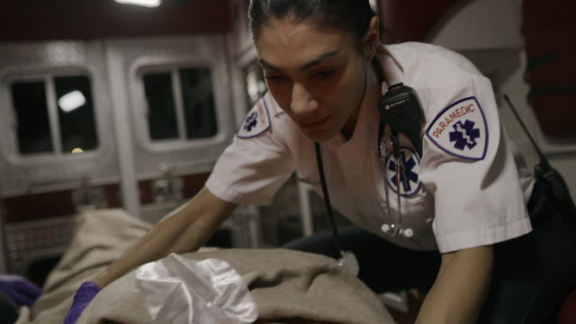 slow motion shot of paramedics comforting and talking to patient in ambulance / lehi, utah, united states - ambulance stock videos & royalty-free footage