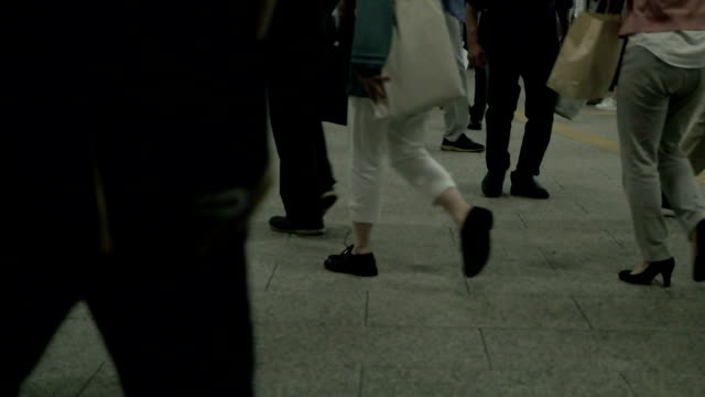 Slow motion shot of pedestrains in Tokyo at night.
