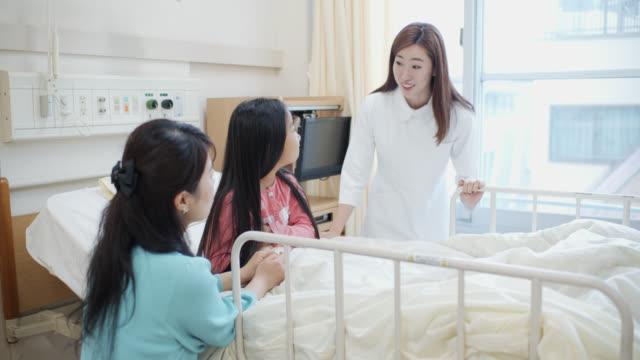 vídeos de stock, filmes e b-roll de tiro lento da enfermeira pediatra que reassegura a matriz e a criança na divisão do hospital - enfermeira pediátrica
