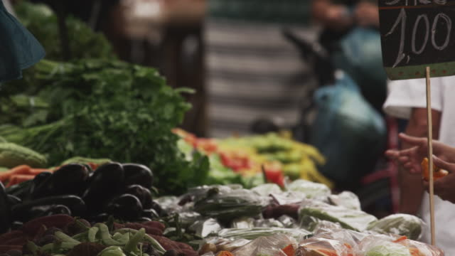 slow motion shot of people buying produce in a market in rio de janeiro, brazil - leaf vegetable stock videos & royalty-free footage