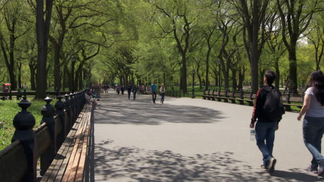 Slow motion shot of people walking on a path near the Bethesda Fountain in Central Park, NYC