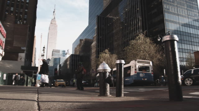 slow motion shot of people walking on the streets in front of the empire state building - fire hydrant stock videos & royalty-free footage