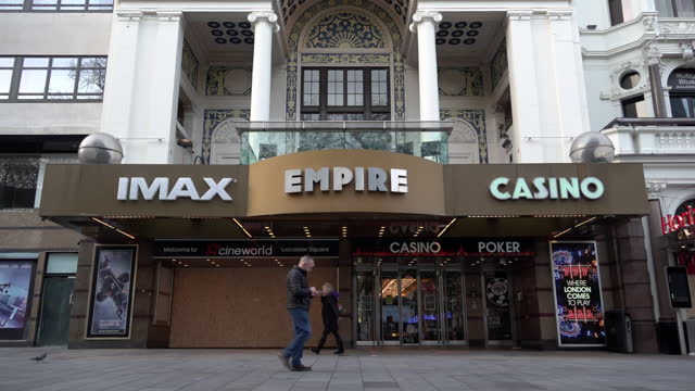 slow motion shot of people wearing face masks walking past the boarded up entrance to the imax empire cinema in leicester square on november 07, 2020... - cinema stock videos & royalty-free footage