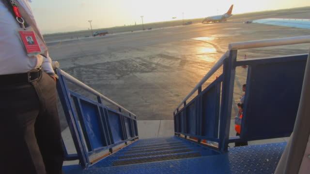 slow motion shot of pilot standing on staircase outside airplane while ground staff at airport runway against sky during sunset - lima, peru - ground staff stock videos & royalty-free footage