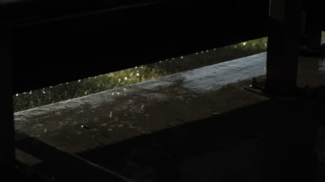 slow motion shot of raining falling onto the bottom of a bus shelter. - raindrop stock videos & royalty-free footage