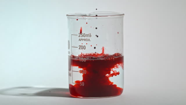 slow motion shot of red dye being dropped into a laboratory glass beaker of water. - blood stock videos & royalty-free footage