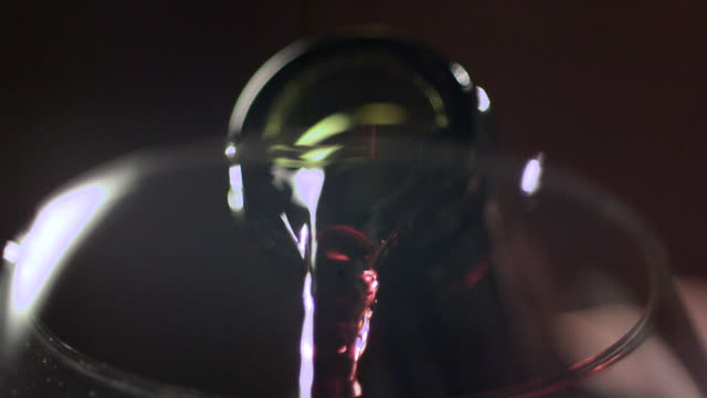 Slow motion shot of red wine being poured into a wine glass.