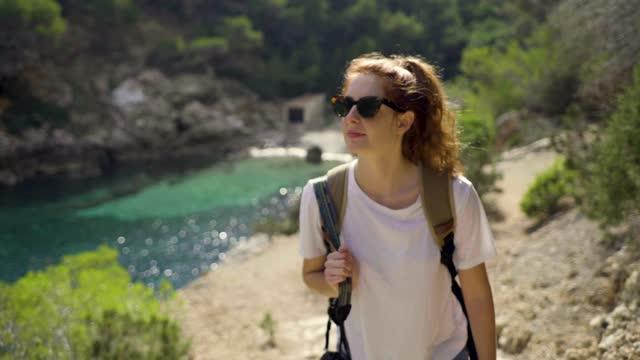 slow motion shot of redheaded woman walking at coast in ibiza - バレアレス点の映像素材/bロール