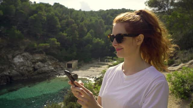 slow motion shot of redheaded woman walking at coast in ibiza - long stock videos & royalty-free footage