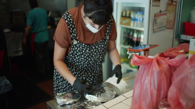 stockvideo's en b-roll-footage met slow motion shot van restaurant personeel samen te stellen orders tijdens covid-19 lockdown - beschermend masker werkkleding
