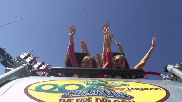 slow motion shot of riders the hood of a roller coaster car - rollercoaster stock videos & royalty-free footage