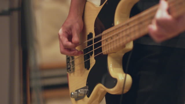 slow motion shot of rock band recording in studio. - エレキギター点の映像素材/bロール