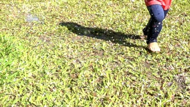 Zeitlupe erschossen von jungen laufen und spielen Sprinkler ausgeführt.