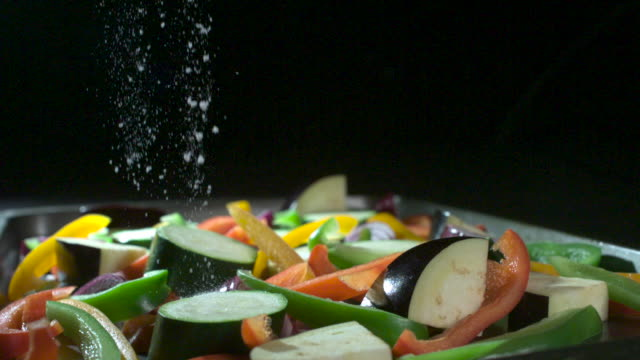 slow motion shot of salt being sprinkled over a pan of chopped vegetables. - chopped food stock videos and b-roll footage