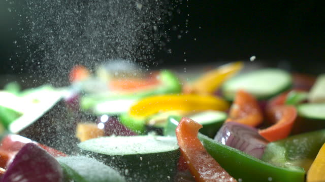 Slow motion shot of salt being sprinkled over a pan of chopped vegetables.