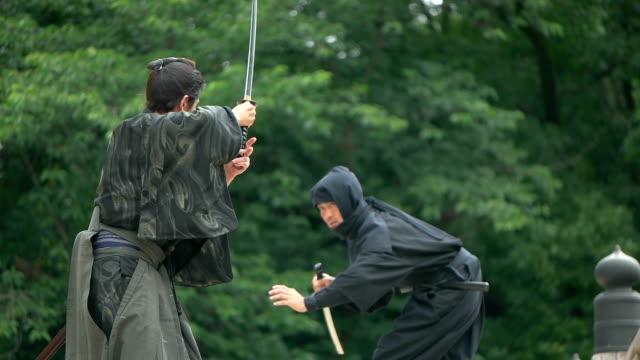 vidéos et rushes de le mouvement lent coup de samouraï et ninja sur le pont. - se battre
