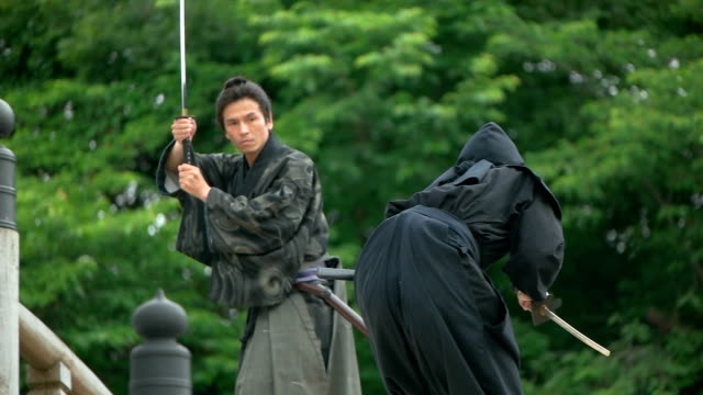 vídeos de stock e filmes b-roll de slow motion shot of samurai and ninja on the bridge. - samurai