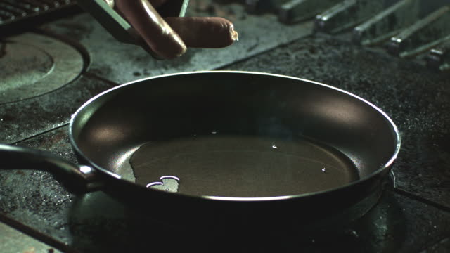 slow motion shot of sausages being dropped into a hot frying pan. - cooking pan stock videos & royalty-free footage